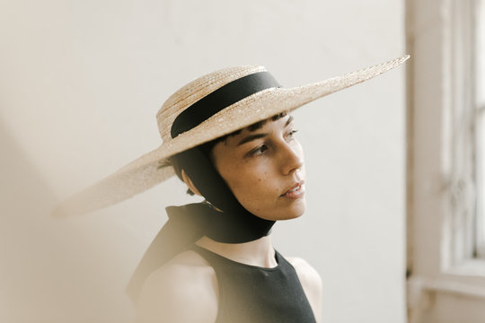 dreamy portrait of woman wearing large straw hat with gold light leak