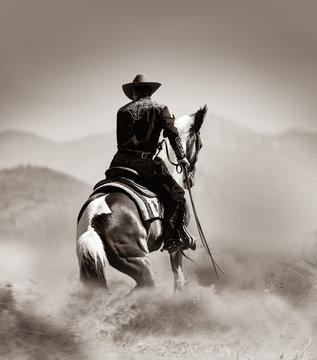 cowboy on a horse running in desert