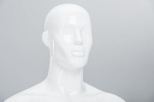 white plastic mannequin doll on grey with copy space