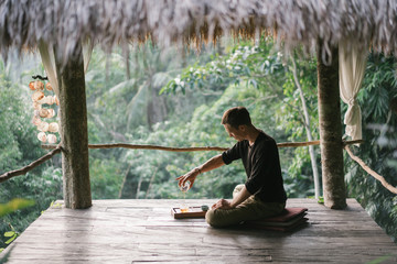 Man pouring tea on exotic terrace