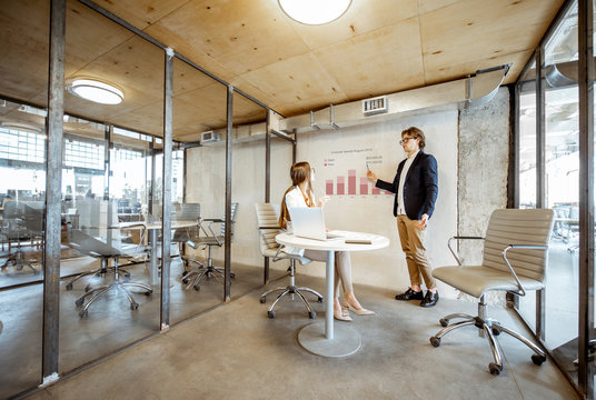 Man showing chart to his female business partner during the small conference in the meeting room