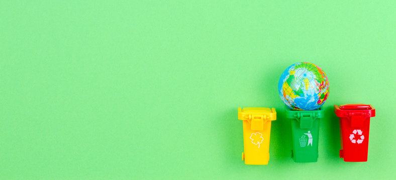 Ecology problem of environmental pollution planet, consumerism, recycling concept. Mini recycle bins containers with globe on green background