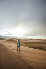 young boy overlooking sand dunes at sunset, mongolia