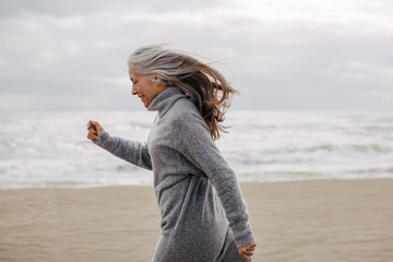 Active senior woman walking on the beach in winter.