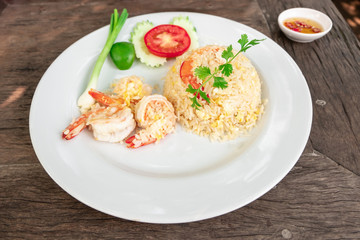 Thai fried rice with prawns tomato, cucumber, spring onions finely sliced and fresh coriander on the white plate