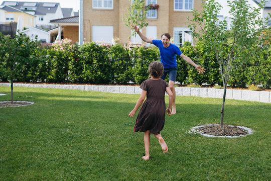 Father fools around with daughter on the lawn