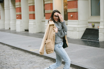 Stylish young woman crossing the street in the city