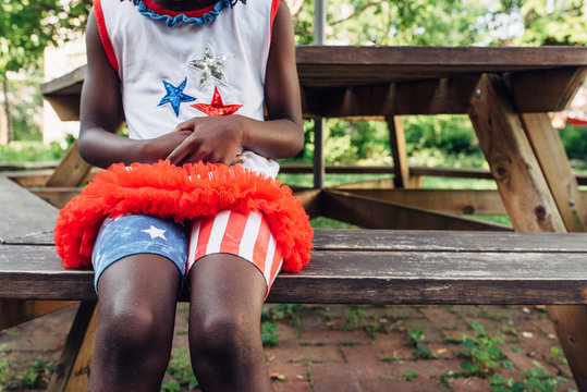 Black girl with USA flag themed outfit sitting on a bench
