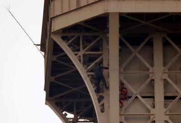 Unidentified man climbs the Eiffel Tower in Paris