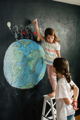 Young girl's drawing planet earth on a blackboard