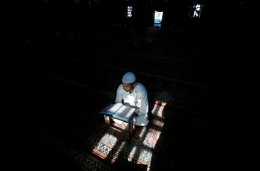 A Kashmiri Muslim man reads the Koran inside the shrine of Mir Syed Ali Hamdani, a Sufi saint, during the holy month of Ramadan in Srinagar