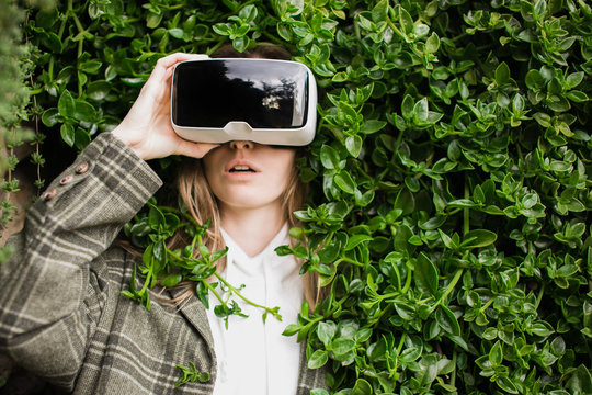 Blond girl in VR headset trapped in a green hedge