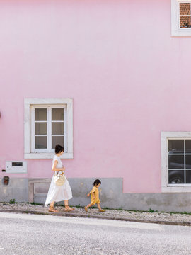 Mom and baby walking down street in front of pink wall