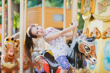 Adorable little toddler girl riding on animal on roundabout carousel in amusement park. Happy healthy baby child having fun outdoors on sunny day. Family weekend or vacations Wall mural