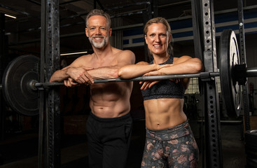 Sportliches Paar mittleren Alters hat zusammen Spaß beim Sport. Die sportliche blonde Frau in den Vierzigern und der durchtrainierte Sportler in den Fünfzigern beim Krafttraining am Reck Wall mural