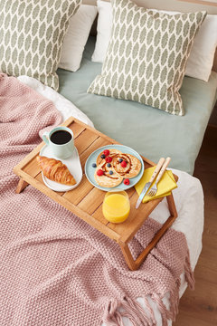 Wooden tray with tasty homemade breakfast.