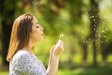Beautiful young woman blowing dandelion