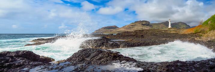 Panorama landscape of waves splashing on the rocky shore at Kukii Point lighthouse, Kalapaki, Kauai, Hawaii, USA