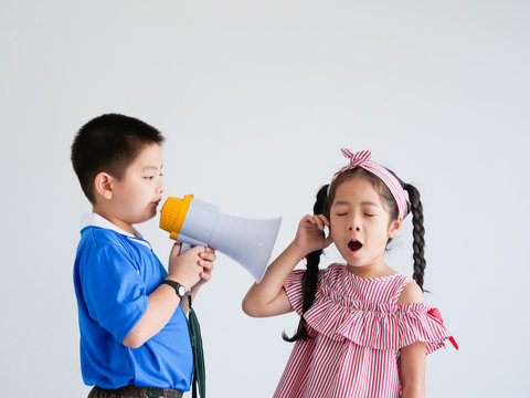Asian cute boy and girl with megaphone singing on white background
