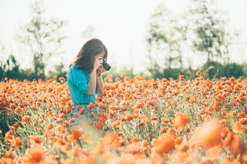 Woman taking a photo with camera the poppy field.