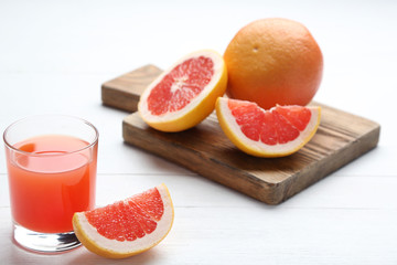 Wall Mural - Ripe grapefruits and glass of juice on white wooden table