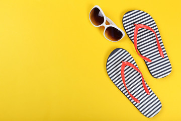 Pair of flip flops with sunglasses on yellow background