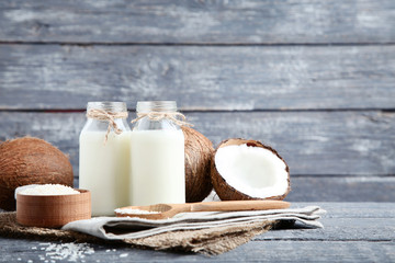 Wall Mural - Coconut milk in bottles with flakes on grey wooden table