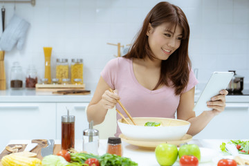 Young asian woman read tablet study information for take care her health by eating salad and fruit instead of eating fat and calories