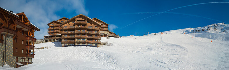 Wall Mural - Slope in alpine ski resort with apartment buildings