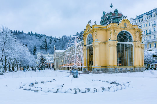Marianske Lazne, Czech Republic - December 28 2017: Winter image of Colonnade made of cast iron. Singning water fountain in front, all covered with white snow.