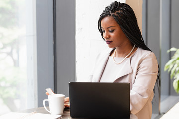 Businesswoman looks at phone next to laptop