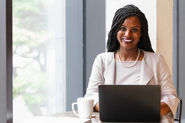 Smiling businesswoman works on laptop