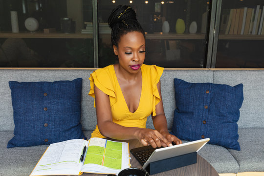 Businesswoman working on laptop next to notebook