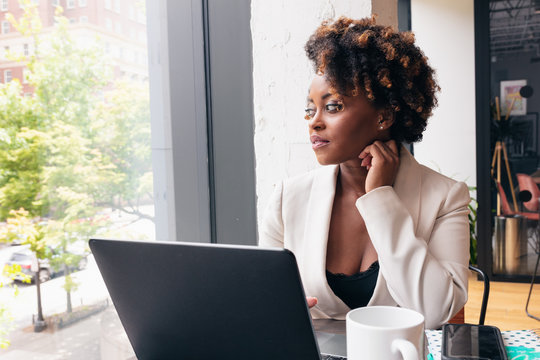 Businesswoman looks out window while sitting by laptop