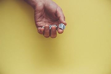 Playing dice in hand, isolated on yellow background.