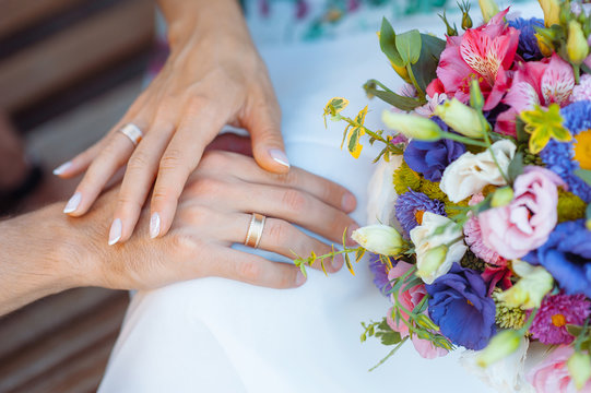Hands with rings on the fingers of the bride and groom on the background of a wedding bouquet