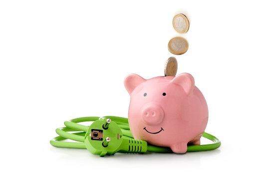 Energie Kosten - Strom sparen ist gut für den Klimaschutz und spart Geld. Euro Münzen fallen in das Sparschwein. Neben dem Sparschwein Liegt ein grünes Stromkabel mit Stecker