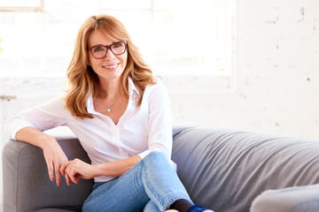 Portrait of attractive middle aged woman relaxing on sofa