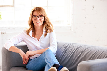 Portrait of attractive middle aged woman relaxing on sofa Wall mural