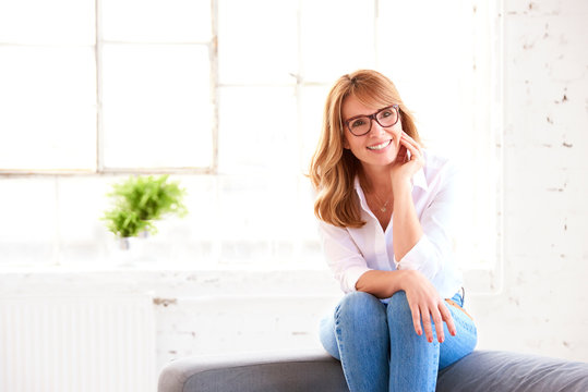 Portrait of beautiful middle aged woman relaxing on sofa