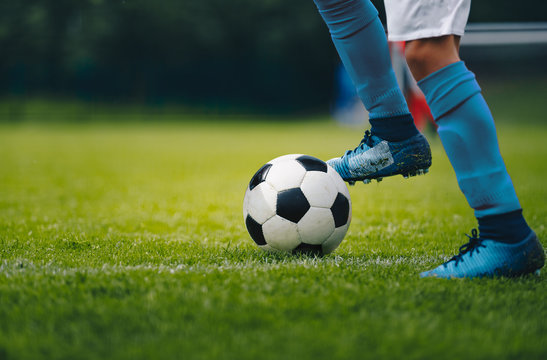 Close up of legs and feet of football player in blue socks and shoes running and dribbling with the ball. Soccer player running after the ball. Sports venue in the background