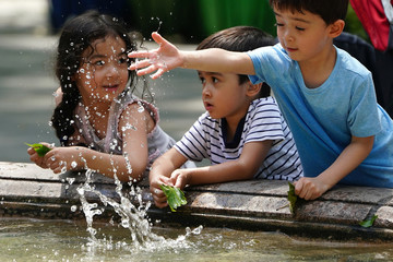 Children play in a fountain in Bryant Park in the Manhattan borough of New York, New York