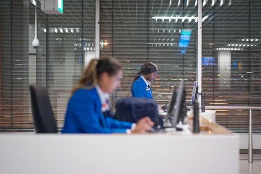 Blurred photo of two flight attendant flight attendants. Two girls of the airport clerk check information about passengers boarding flight in the computer.