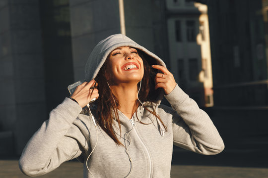 Young woman in gray hoodie enjoys music via headphones on the street