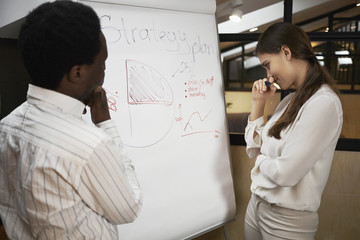 People, education, job, career and teamwork concept. Picture of dark skinned man and Caucasian woman standing at flip chart with thoughtful pensive facial expressions, having brainstorming session