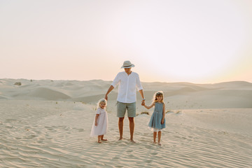 Young father having fun with his daughters in the desert