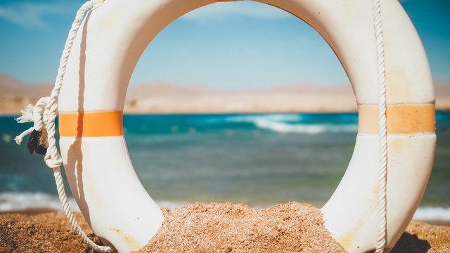 Closeup image of beautiful sea beach and white plastic kife saving ring at bright sunny day. Perfect shot to illustrate summer holiday vacation at ocean.