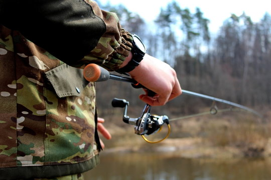 Angler in camouflage clothing, fishing on spinning