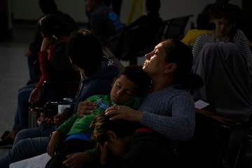 Sonia, an asylum seeker from Honduras, waits with sleeping six-year-old son Yankel and daughter Yarisleidy, twins, before boarding a bus with fellow migrant families recently released from detention at a bus depot in McAllen