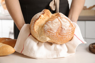 Baker with loaf of bread at table indoors, closeup